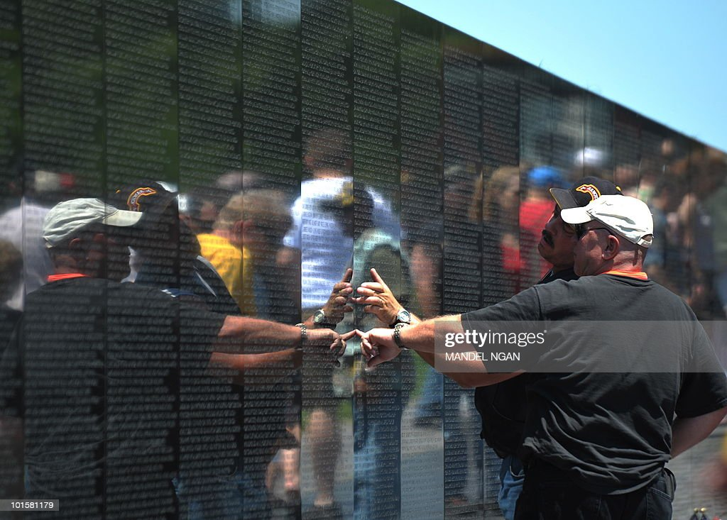 Visitors pay their respects at the Vietnam Veterans Memorial on May 30, 2010 in Washington. The wall is inscribed with the names of servicemen who were killed or are missing in action from the war in Vietnam. AFP PHOTO/Mandel NGAN