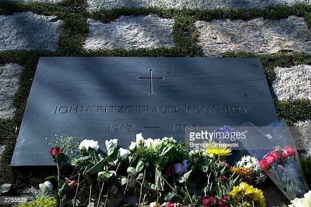 Visitors pay their respects by leaving flowers at the grave of assassinated US President John F Kennedy in Arlington National Cemetery November 22...
