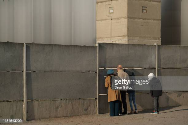 Visitors peek from the inner wall into the death zone at a preserved portion of the Berlin Wall at Bernauer Strasse on October 31 2019 in Berlin...