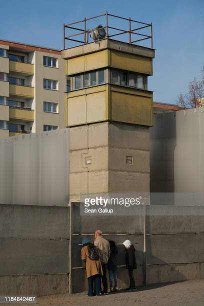 Visitors peek from the inner wall into the death zone under an original East German guard tower at a preserved portion of the Berlin Wall at Bernauer...