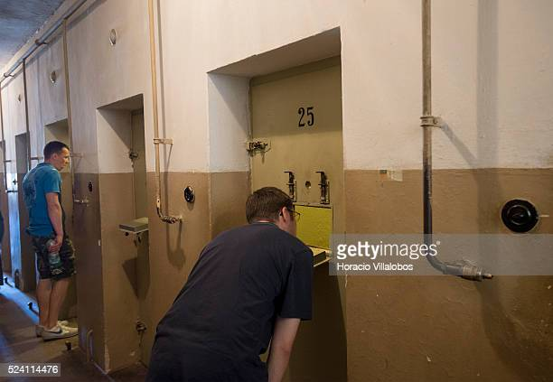 Visitors peer into the cells at the 'Bunker' or cell block in Buchenwald concentration camp near Weimar Germany 21 July 2013 The camp established by...