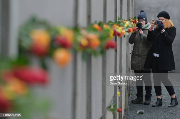 Visitors photograph flowers stuck into slats of a stillstanding portion of the Berlin Wall at Bernauer Strasse following a ceremony to celebrate the...
