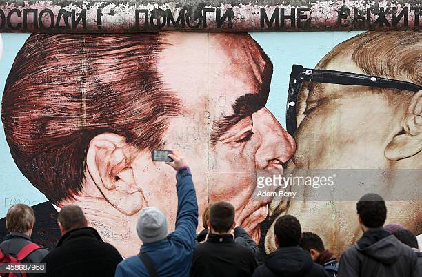 Visitors photograph graffiti by Dmitri Vrubel of General Secretary of the Central Committee of the Communist Party of the Soviet Union Leonid...