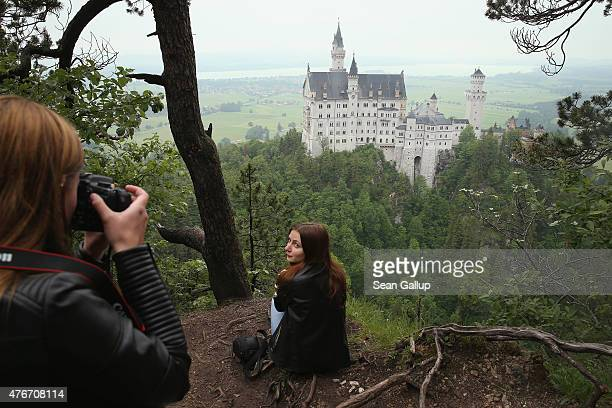 Visitors photograph one another from a forest path overlooking Schloss Neuschwanstein castle on June 10 2015 near Hohenschwangau Germany Schloss...