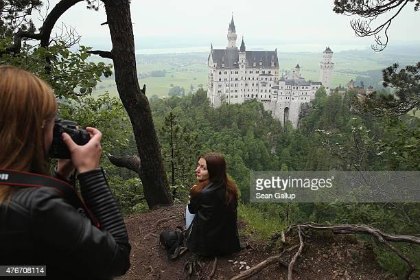 Visitors photograph one another from a forest path overlooking Schloss Neuschwanstein castle on June 10 2015 near Hohenschwangau Germany Schloss...