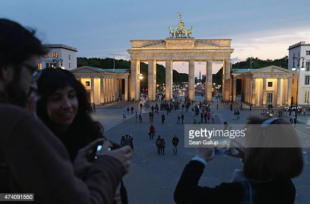Visitors photograph Pariser Platz square and the Brandenburg Gate from atop a temporary viewing platform on May 19 2015 in Berlin Germany Berlin is...