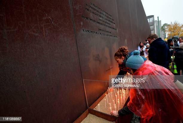 Visitors place candles at the Berlin Wall Memorial during the central commemoration ceremony for the 30th anniversary of the fall of the Berlin Wall,...