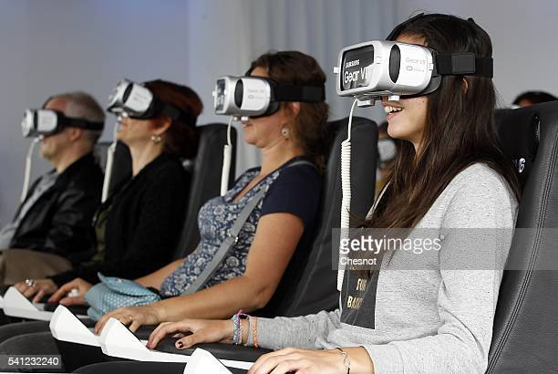 Visitors play a game with the virtual reality headmounted Samsung Gear VR powered by Oculus at 'S7 Life Changer Park' on June 19 2016 in Paris France...