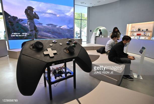 Visitors play games next to a big model of Microsoft's Xbox controller at a flagship store of SK Telecom in Seoul on November 10, 2020.