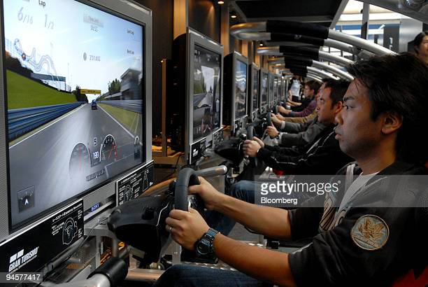 Visitors play Gran Turismo a racing video game at the 40th Tokyo Motor Show 2007 in Chiba City Japan on Wednesday Oct 24 2007 Media previews for the...