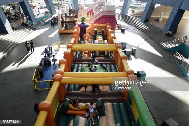Visitors play in an inflatable playground in an entertainment area of the SM Mall of Asia complex operated by SM Prime Holdings Inc in Pasay City...