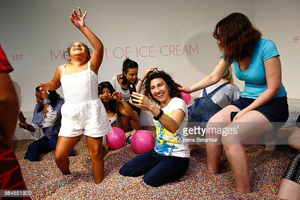 Visitors play into a large pool filled with faux confetticolored sprinkles at the Museum of Ice Cream across from the Whitney Museum on July 29 2016...