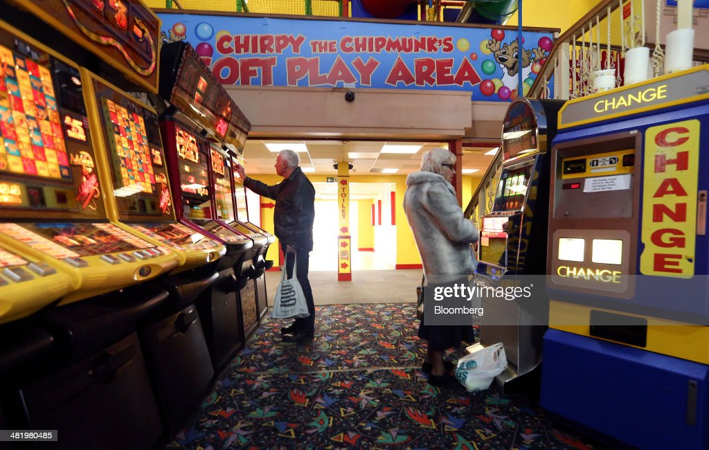 Visitors play on slot machines inside a games arcade on Eastbourne Pier in Eastbourne, U.K., on Tuesday, April 1, 2014. Pensioners and savers have seen returns on their money shrink since the financial crisis drove interest rates to a record low. Photographer: Chris Ratcliffe/Bloomberg via Getty Images