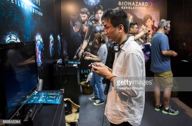 Visitors play the Biohazard revelations 2 video game on Nintendo Co's Switch game consoles in the Capcom Co booth during the Tokyo Game Show 2017 at...