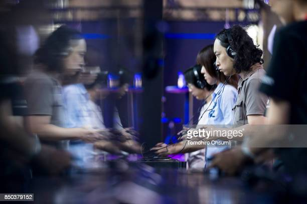 Visitors play the Final Fantasy XV video game in the Square Enix Holdings Co. Booth during the Tokyo Game Show 2017 at Makuhari Messe on September...