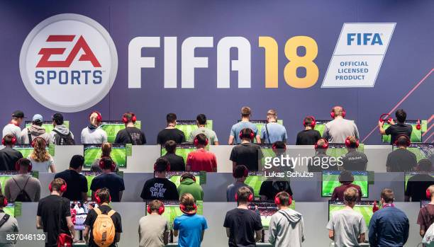 Visitors play the soccer game FIFA18 while visiting the Gamescom 2017 video gaming trade fair on August 22 2017 in Cologne Germany Gamescom is the...
