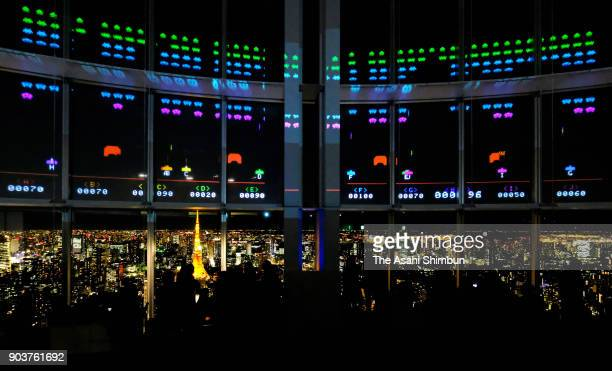 Visitors play the 'Space Invaders Giga Max' projected on the window of the Roppongi Hills during the press preview on January 11 2018 in Tokyo Japan...