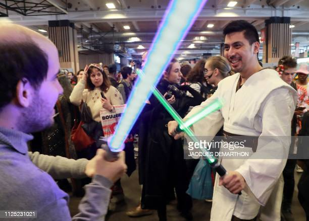 Visitors play with lightsabers as they attend the Paris Manga and Scifi show at the Porte de Versailles in the southwest of Paris on February 16 2019