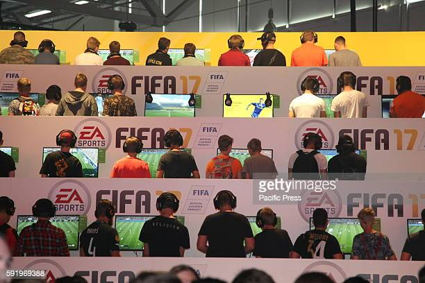 Visitors playing Fifa 17 at the EA Sports stand at the Gamescom fair Gamescom the Worlds largest Gaming Fair Gamescom is a trade fair for video games...