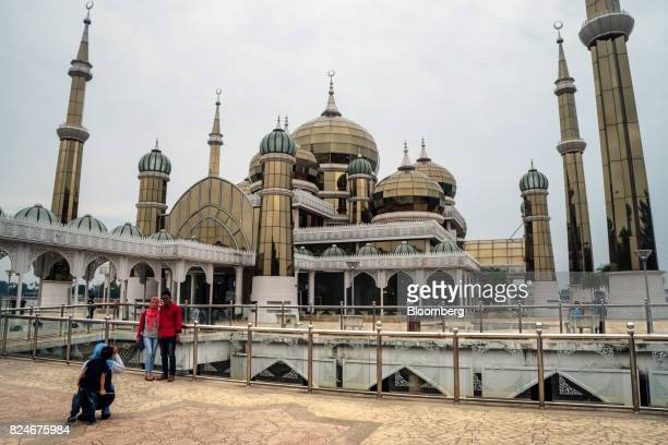 Visitors pose for a photograph outside the Crystal Mosque in Kuala Terengganu Terengganu Malaysia on Monday July 23 2017 With a federal election due...