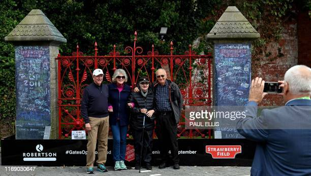 Visitors pose for a photograph with the original gates to Strawberry Field at inside the newly opened centre in Liverpool northwest England on...