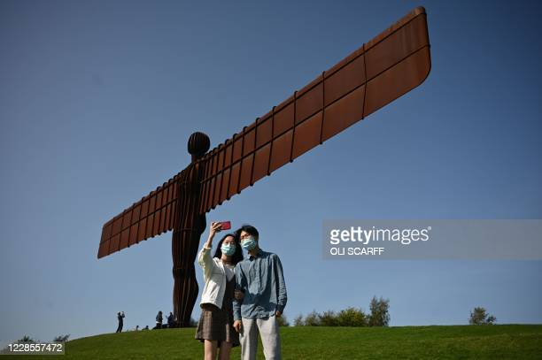TOPSHOT Visitors pose for photographs at the iconic sculpture designed by Antony Gormley 'Angel of the North' in Gateshead northeast England on...