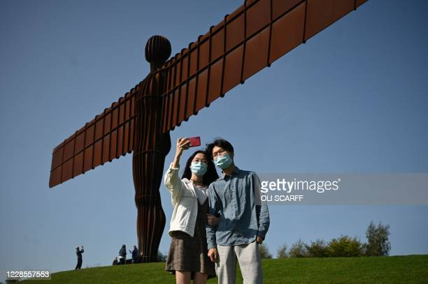 Visitors pose for photographs at the iconic sculpture designed by Antony Gormley 'Angel of the North' in Gateshead, northeast England, on September...
