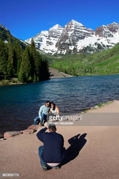 Visitors pose for photographs beside Maroon Lake Maroon Lake and the Maroon Bells in the background are popular outdoor recreation destinations near...