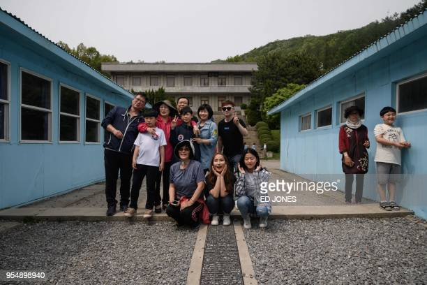Visitors pose for photos at a replica of the DMZ border truce village of Panmunjom built as a film set near Namyangju east of Seoul on May 5 2018...