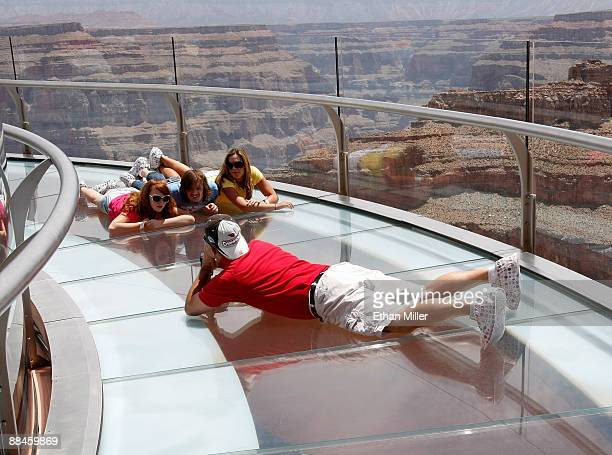 Visitors pose for photos at the Grand Canyon Skywalk June 12 2009 in Grand Canyon West Arizona The Skywalk is a oneofakind glass bottom cantilever...