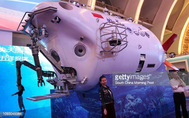 Visitors pose for photos in front a model of China's deepsea manned submersible Jiaolong at a special exhibition celebrating the achievements in the...