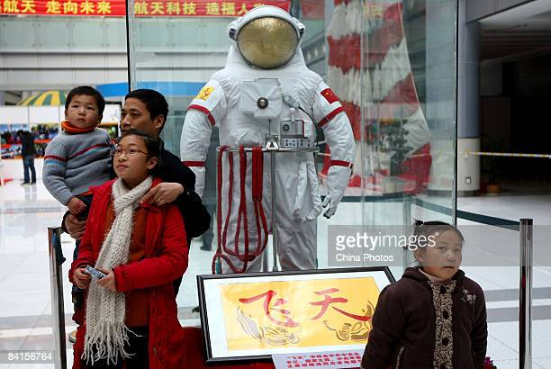 Visitors pose for photos in front of the Feitian space suit wore by astronauts of Shenzhou VII spacecraft during China's third manned space mission...