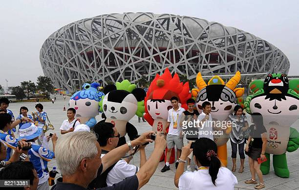 Visitors pose for photos next to 2008 Beijing Olympic mascots in front of the National Stadium, which is also known as the Bird's Nest, in Beijing on...