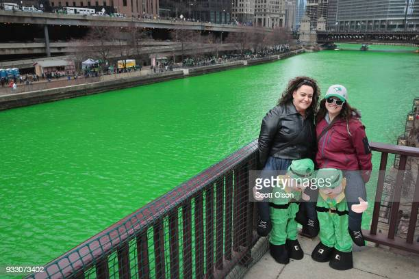 Visitors pose for pictures along the Chicago River shortly after it was dyed green in celebration of St Patrick's Day on March 17 2018 in Chicago...