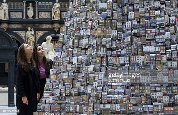 Visitors pose for pictures beside an artwork entitled 'The Tower of Babel' by British artist Barnaby Barford during a photocall at the Victoria...