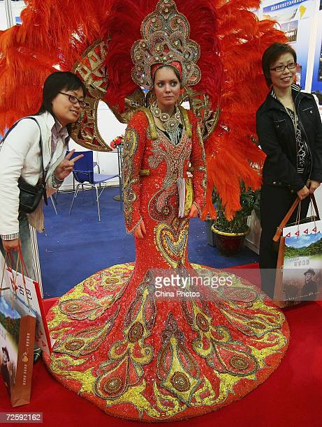 Visitors pose for pictures with a worker dressed in traditional costume in the Argentina pavilion at the 2006 China International Travel Mart on...