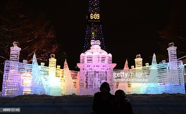 Visitors pose in front of an ice sculpture of the Palace of the Heart during the 65th annual Sapporo Snow Festival in Sapporo on February 5 2014 The...