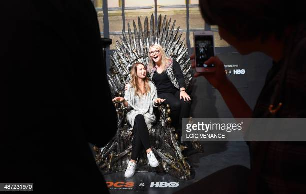 Visitors pose on the Iron Throne on September 7 2015 during the opening of an exhibition dedicated to HBO's television medieval fantasy series Game...