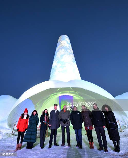 Visitors pose with a 305metretall ice tower named 'Flamenco Tower' during 2017 Harbin International Ice and Snow Construction Festival at Maple Leaf...