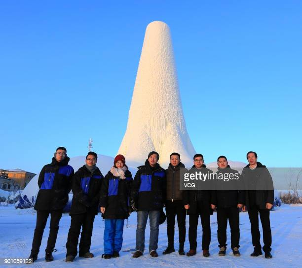 Visitors pose with a 30metretall ice tower during 2017 Harbin International Ice and Snow Construction Festival at Maple Leaf Village on January 3...
