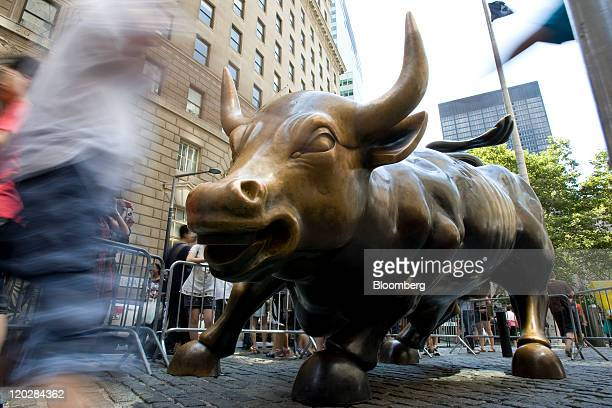 Visitors pose with a bull statue near the New York Stock Exchange in New York US on Wednesday Aug 3 2011 US stocks were little changed following the...