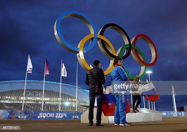 Visitors pose with a Russian flag inside Olympic Park in front of the Bolshoy Ice Dome at the Winter Olympics in Sochi Russia Thursday Feb 6 2014