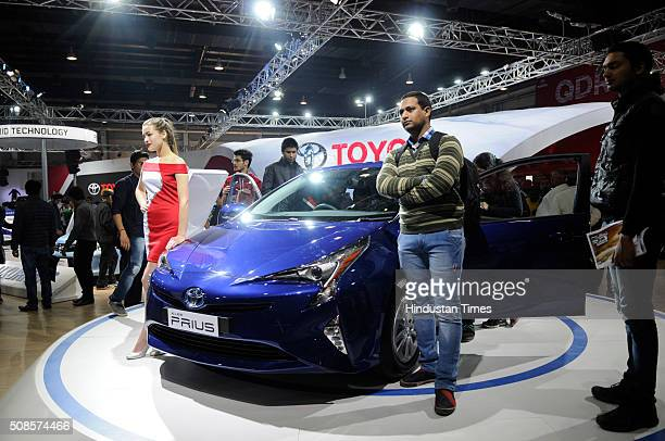 Visitors pose with Toyota Prius car at Auto Expo 2016 on February 5 2016 in Greater Noida India The 13th edition of the Delhi Auto Expo kicked off at...