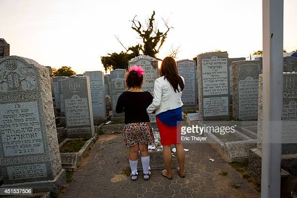 Visitors pray at the gravesite of the Lubavitcher Rebbe Rabbi Menachem Mendel Schneerson June 30 2014 at the Old Montefiore Cemetery in the Queens...