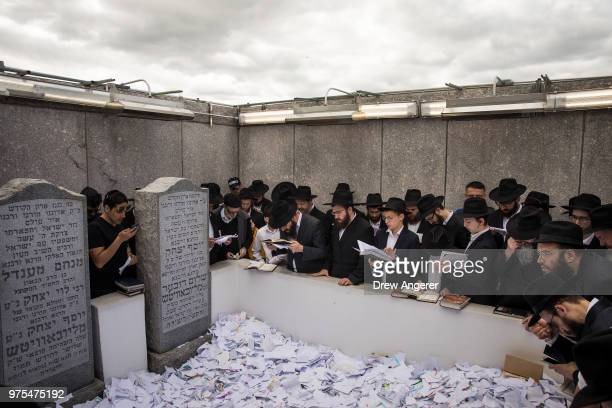 Visitors pray at the gravesite of the Lubavitcher Rebbe Rabbi Menachem Mendel Schneerson at the Old Montefiore Cemetery June 15 2018 in the Queens...