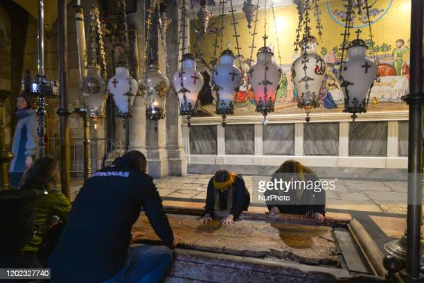 Visitors pray at the Stone of Anointing where Jesus' body is said to have been anointed before burial inside the Holy Sepulchre church in the Old...