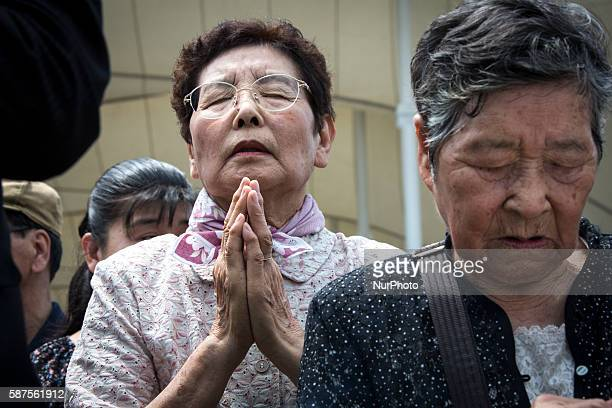 Visitors pray for the atomic bomb victims in front of the Peace Statue during the 71st Anniversary of atomic bombing on Nagasaki at Nagasaki Peace...