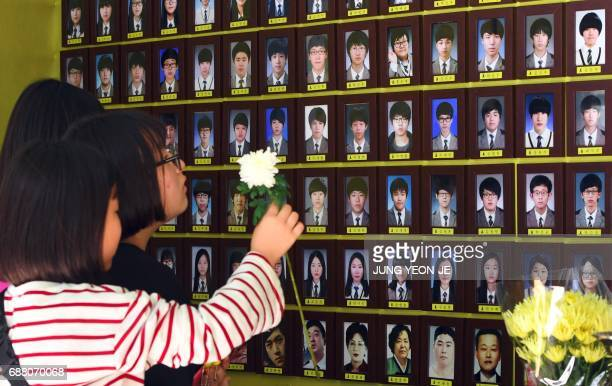 Visitors pray in front of portraits of victims of the 2014 South Korea's Sewol ferry disaster at a memorial altar in Seoul on May 25 2017 A third set...