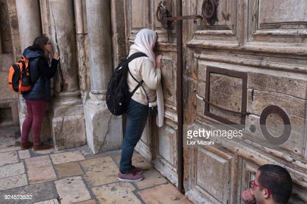 Visitors pray outside the closed gate to the Church of the Holy Sepulcher in the Old City on February 26 2018 in Jerusalem Israel The Jerusalem...