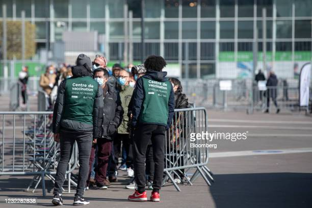 Visitors queue outside the Stade de France vaccination center in Paris, France, on Tuesday, April 13, 2021. The French economy is slowing only...
